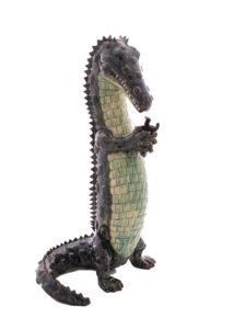 La supplication est une sculpture de Valérie Courtet représentant un crocodile se tenant debout et tenant un oiseau entre ses pattes antérieures, presque en prière.